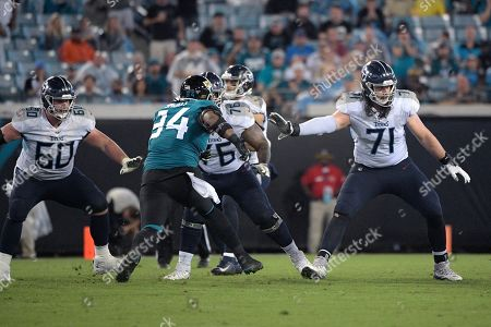 Tennessee Titans center Ben Jones (60), offensive guard Rodger Saffold (76) and offensive tackle Dennis Kelly (71) set up to block during the second half of an NFL football game against the Jacksonville Jaguars, in Jacksonville, Fla
