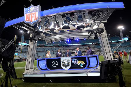 The NFL Network's Thursday Night Football television team of Colleen Wolfe, left, Steve Smith, second from left, Maurice Jones-Drew, center, Joe Thomas and Michael Irvin, right, broadcast from their set after an NFL football game between the Jacksonville Jaguars and the Tennessee Titans, in Jacksonville, Fla