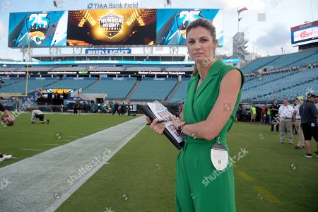 Fox Sports sideline reporter Erin Andrews watches warmups before an NFL football game between the Jacksonville Jaguars and the Tennessee Titans, in Jacksonville, Fla