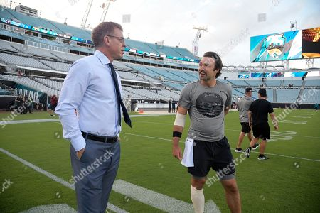 Fox Sports analyst Troy Aikman, left, talks with Jacksonville Jaguars quarterback Gardner Minshew on the field before an NFL football game against the Tennessee Titans, in Jacksonville, Fla