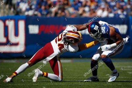 Josh Norman, Darius Slayton. Washington Redskins cornerback Josh Norman (24) tries to bring down New York Giants wide receiver Darius Slayton (86) during an NFL football game, in East Rutherford, N.J. The Giants won the game 24-3