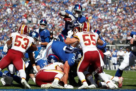 Cole Holcomb, Wayne Gallman. New York Giants running back Wayne Gallman (22) tries to leap over the goal line but was stopped by Washington Redskins linebacker Cole Holcomb (55)during an NFL football game, in East Rutherford, N.J. The Giants won the game 24-3