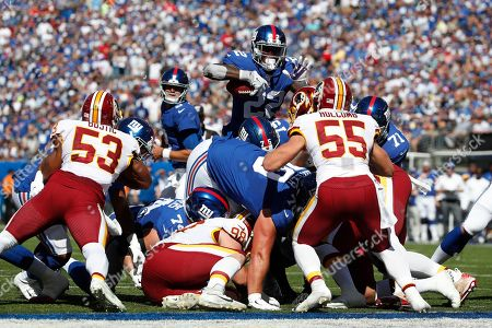 Stock Image of Cole Holcomb, Wayne Gallman. New York Giants running back Wayne Gallman (22) tries to leap over the goal line but was stopped by Washington Redskins linebacker Cole Holcomb (55)during an NFL football game, in East Rutherford, N.J. The Giants won the game 24-3
