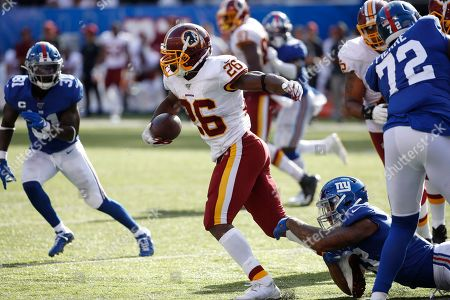 Washington Redskins running back Adrian Peterson (26) runs with the ball during an NFL football game New York Giants, in East Rutherford, N.J. The Giants won the game 24-3
