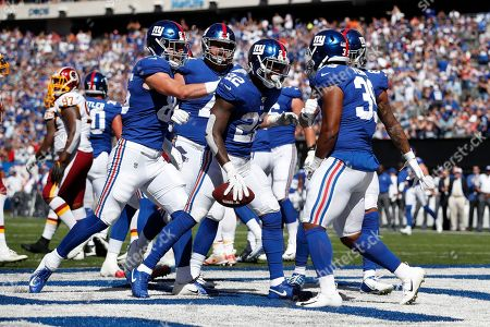 New York Giants running back Wayne Gallman (22) celebrates a touchdown against the Washington Redskins with teammates during an NFL football game, in East Rutherford, N.J. The Giants won the game 24-3