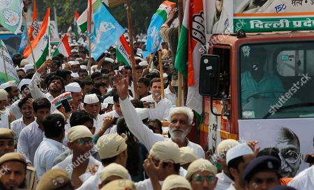 Congress party leader Rahul Gandhi, center joins party workers in a procession to mark the 150th anniversary of iconic independence leader Mahatma Gandhi in New Delhi, India