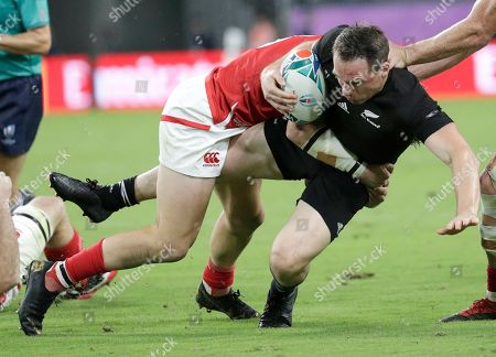 New Zealand's Ben Smith is tackled by a Canadian defender during the Rugby World Cup Pool B game at Oita Stadium between New Zealand and Canada in Oita, Japan