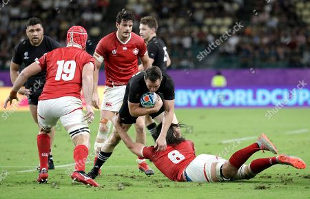 New Zealand's Ben Smith attempts to evade the tackle of Canada's Tyler Ardron, right, and Mike Sheppard, left, during the Rugby World Cup Pool B game at Oita Stadium between New Zealand and Canada in Oita, Japan