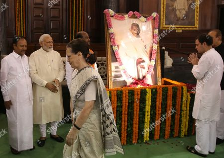 Indian Prime Minister Narendra Modi, second left, watches Congress party leader Rahul Gandhi, right, pay tribute in front of a portrait of Mahatma Gandhi, as Congress President Sonia Gandhi walks past, on the 150 birth anniversary of Mahatma Gandhi, at the Parliament House in New Delhi, India