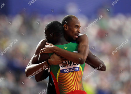 Steven Gardiner, of the Bahamas embraces Kirani James, of Grenada after racing in a men's 400 meter semifinal at the World Athletics Championships in Doha, Qatar