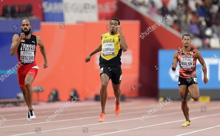 Akeem Bloomfield, of Jamaica, center, Machel Cedenio, of Trinidad And Tobago, left, and Julian Jrummi Walsh, of Japan, right, race in a men's 400 meter semifinal at the World Athletics Championships in Doha, Qatar