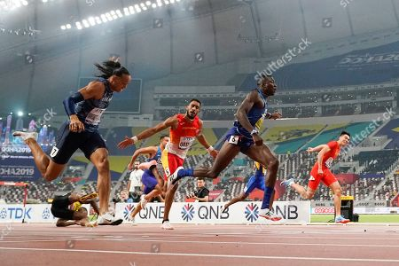 Gold medallist Grant Holloway, of the United States, second from right, crosses the finish line ahead of Pascal Martinot-Lagarde, of France, left, and Orlando Ortega, of Spain, center, to win the men's 110 meter hurdles final at the World Athletics Championships in Doha, Qatar, . At lower left is Jamaica's Omar Mcleod, who fell when clearing the last hurdle
