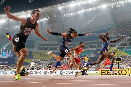 Gold medallist Grant Holloway, of the United States, right, crosses the finish line ahead of Pascal Martinot-Lagarde, of France (7), and Orlando Ortega, of Spain (5), to win the men's 110 meter hurdles final at the World Athletics Championships in Doha, Qatar, . At lower left is Jamaica's Omar Mcleod, who fell when clearing the last hurdle