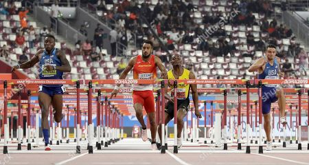 Omar Mcleod, of Jamaica, second right, stumbles into Orlando Ortega, of Spain as Grant Holloway, of the United States, left, races to gold in the men's 110 meter hurdles final at the World Athletics Championships in Doha, Qatar