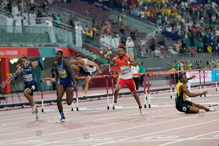 Omar Mcleod, of Jamaica, right, falls as Pascal Martinot-Lagarde, of France, left; Grant Holloway, of the United States, second from left; and Orlando Ortega, of Spain, second from right; finish the men's 110 meter final at the World Athletics Championships in Doha, Qatar