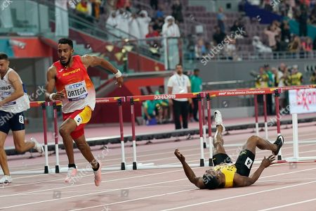 Omar Mcleod, of Jamaica, right, falls as Orlando Ortega, of Spain, finishes the the men's 110 meter hurdles final during the World Athletics Championships in Doha, Qatar