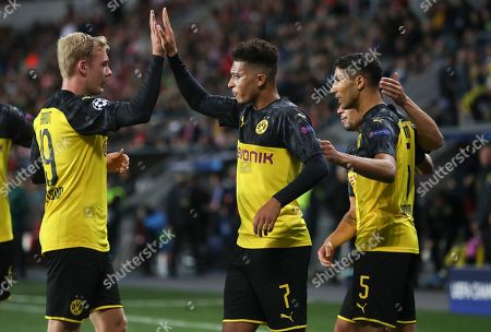 Achraf Hakimi of Borussia Dortmund (R) celebrates after scoring the 1-0 lead with team mates Jadon Sancho (C) and Julian Brandt (L) during the UEFA Champions League Group F match between Slavia Prague and Borussia Dortmund in Prague, Czech Republic, 02 October 2019.