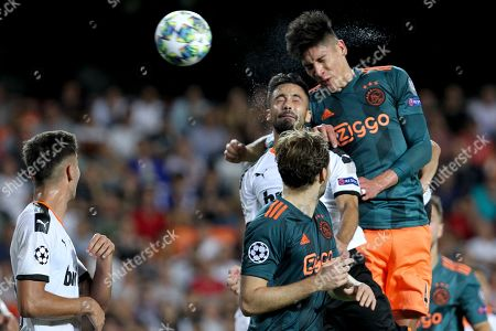 Ajax's Edson Alvarez, top, jumps for the ball against Valencia's Jaume Costa during the Champions League group H soccer match between Valencia and Ajax, at the Mestalla stadium in Valencia