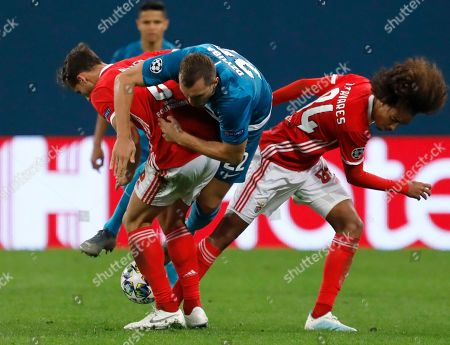 Zenit's Artem Dzyuba, center, fights for the ball with Benfica's Ruben Dias, left, and Benfica's Tomas Tavares during the Champions League group G soccer match between Zenit St.Petersburg and Benfica at the Saint Petersburg stadium in St.Petersburg, Russia