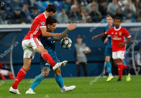 Benfica's Ruben Dias, left, fights for the ball with Zenit's Sebastian Driussi during the Champions League group G soccer match between Zenit St.Petersburg and Benfica at the Saint Petersburg stadium in St.Petersburg, Russia