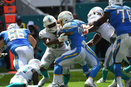 Austin Ekeler #30 of Los Angeles is tackled by Raekwon McMillan #52 of Miami during the NFL football game between the Miami Dolphins and Los Angeles Chargers at Hard Rock Stadium in Miami Gardens FL. The Chargers defeated the Dolphins 30-10