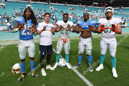 Miami Hurricanes football alumni Rayshawn Jenkins #23, Michael Badgley (t-shirt), and Denzel Perryman #52 of Los Angeles pose with Mark Walton #22 and Trent Harris #97 of Miami during the NFL football game between the Miami Dolphins and Los Angeles Chargers at Hard Rock Stadium in Miami Gardens FL. The Chargers defeated the Dolphins 30-10