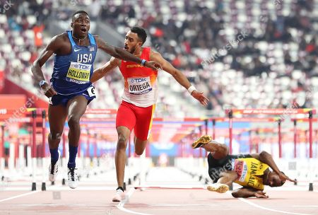 Grant Holloway (L) of the USA crosses the finish line to win the men's 110m Hurdles final as Jamaica's Omar McLeod (R) falls at the IAAF World Athletics Championships 2019 at the Khalifa Stadium in Doha, Qatar, 02 October 2019.