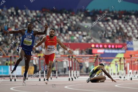 Grant Holloway, of the United States celebrates as he wins the gold medal in the men's 110 meter hurdles final at the World Athletics Championships in Doha, Qatar, . At center is Orlando Ortega, of Spain and at right is Omar Mcleod, of Jamaica who fell