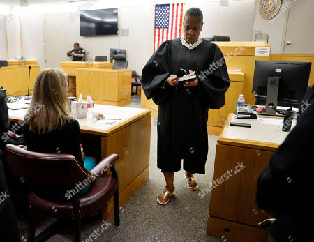 State District Judge Tammy Kemp opens a Bible to John 3:16 before giving it to former Dallas Police Officer Amber Guyger, left, before Guyger left for jail, Wednesday, Oct. 2, 2019, in Dallas. Guyger, who said she mistook neighbor Botham Jean's apartment for her own and fatally shot him in his living room, was sentenced to a decade in prison. (Tom Fox/The Dallas Morning News via AP, Pool)