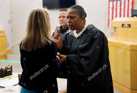 Stock Photo of State District Judge Tammy Kemp gives advice and encouragement to former Dallas Police Officer Amber Guyger, left, before Guyger left for jail, Wednesday, Oct. 2, 2019, in Dallas. Guyger, who said she mistook neighbor Botham Jean's apartment for her own and fatally shot him in his living room, was sentenced to a decade in prison. (Tom Fox/The Dallas Morning News via AP, Pool)