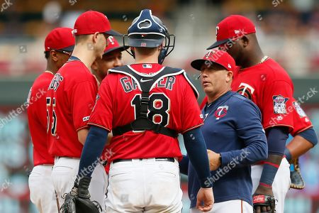 Minnesota Twins pitching coach Wes Johnson, right, holds a meeting on the mound with pitcher Taylor Rogers, left, and catcher Mitch Garver during a baseball game in Minneapolis. Johnson, straight from the college ranks, and a background with biomechanics and an accentuate-the-positive personality, has made a mark on the staff of the American League Central champions