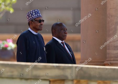 Nigerian President Muhammadu Buhari, left, stands with South Africa's leader Cyril Ramaphosa for the playing of the national anthems at a welcoming ceremony in Pretoria, South Africa . Buhari is visiting after a wave of attacks on foreigners angered many African countries and led to an extraordinary airlift to take hundreds of Nigerians home