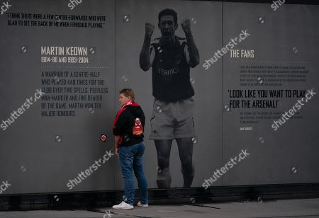 A Standard Liege fan urinates against the stadium wall featuring a cheering Martin Keown