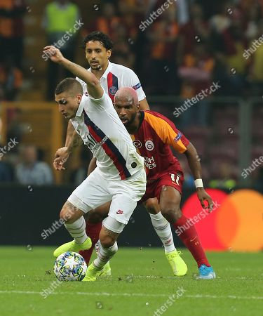 Galatasaray's Steven Nzonzi, center, and PSG's Marco Verratti vie for the ball