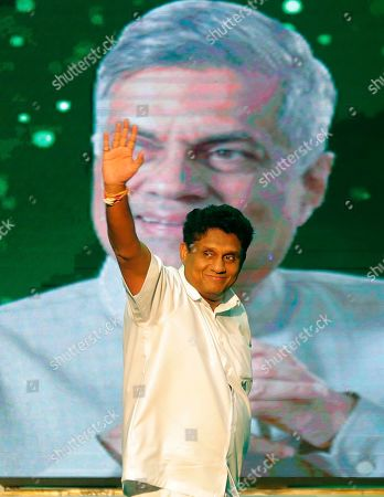 Deputy leader of Sri Lanka's governing United National Party and their presidential candidate Sajith Premadasa waves to supporters as he attends a party convention in Colombo, Sri Lanka, . A photograph of party leader and prime minister Ranil Wickremesinghe is behind