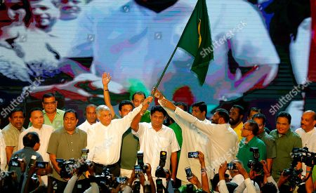 Deputy leader of Sri Lanka's governing United National Party and their presidential candidate Sajith Premadasa, center, along with prime minister Ranil Wickremesinghe, centerleft and other members attend a party convention in Colombo, Sri Lanka