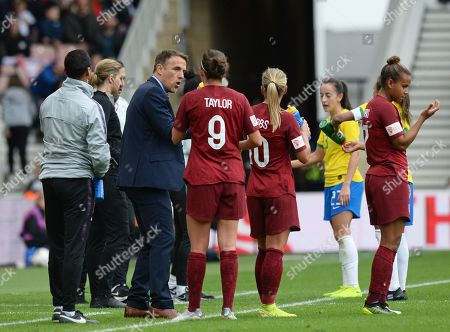 Phil Neville manager of England Women gives instructions to his players during a break in play
