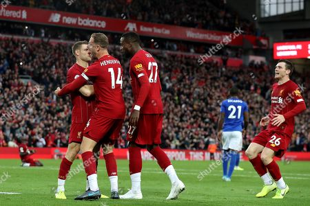 James Milner of Liverpool celebrates scoring his sides second goal from the penalty spot with Jordan Henderson and Divock Origi to make the score 2-1