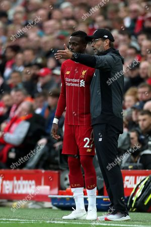 Liverpool Manager Jurgen Klopp speaks with substitute Divock Origi