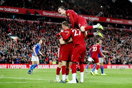 Liverpool players celebrate the second goal scored from the penalty spot by James Milner