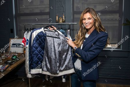 Erin Andrews hold up her favorite item from her fashionable and comfortable WEAR collection, the Satin Bomber Jacket, during a preview event, in New York