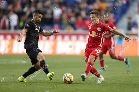 Stock Image of D.C. United midfielder Felipe Martins (18) and New York Red Bulls midfielder Marc Rzatkowski (90) attack the ball during an MLS soccer match, in Harrison, N.J. The final score was a 0-0 draw