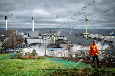 A skier is pulled up an artificial slope of the Amager Bakke/Copenhill building in Copenhagen, Denmark, 03 October 2019. The artificial ski slope and hiking area is built on the roof of the new waste management centre Amager Resource Center in Copenhagen. Copenhill will open 04 October 2019. Amager Bakke is designed by BIG, Bjarke Ingels Group.