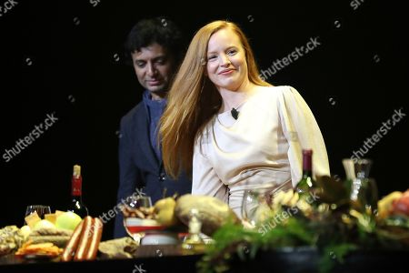 """Lauren Ambrose, right, walks on stage while M. Night Shyamalan looks on during the """"A Night with M. Night: Introducing Servant on Apple TV+"""" panel at Hammerstein Ballroom on the first day of New York Comic Con, in New York"""