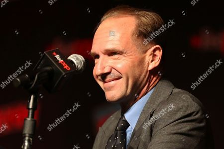 "Stock Photo of Ralph Fiennes smiles on stage during the 20th Century Fox Panel: An Insider's Look at ""The King's Man"" and ""Free Guy"" on the first day of New York Comic Con, in New York"