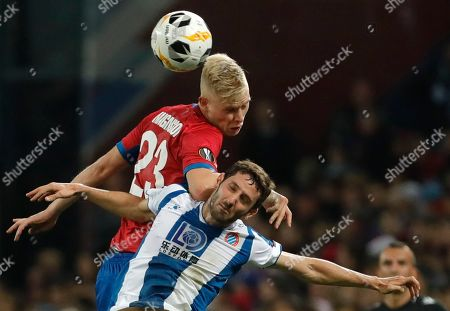 CSKA's Hoerdur Bjoergvin Magnusson, left, and Espanyol's Esteban Granero challenge for the ball during the Europa League group H soccer match between CSKA Moscow and Espanyol at CSKA Arena in Moscow, Russia