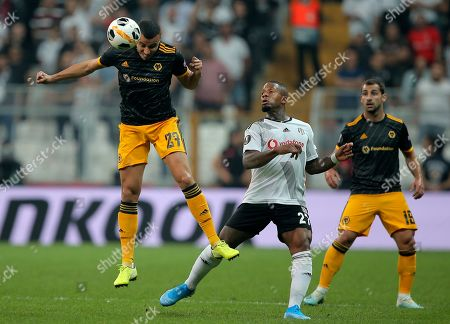 Wolverhampton Wanderers' Romain Saiss, left, heads the ball as Besiktas' Jeremain Lens looks on during the Europa League group K soccer match between Besiktas and Wolverhampton Wanderers at the Besiktas Park in Istanbul