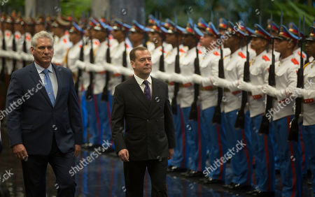 Cuban President Miguel Diaz-Canell, left, and Russian Prime Minister Dmitri Medvedev, inspect and honor guard during Medvedev's arrival at the Council of State in Havana, Cuba