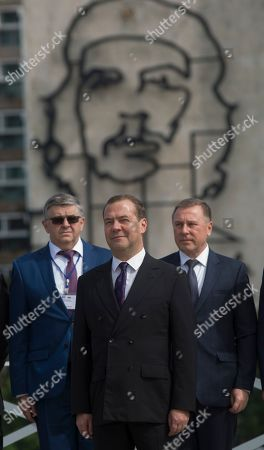 """Russian Prime Minister Dmitri Medvedev, center, poses for a photo with an image of Cuban revolutionary icon Ernesto """"Che"""" Guevara in the background, at Revolution Plaza in Havana, Cuba"""