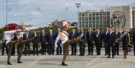 Russian Prime Minister Dmitri Medvedev, third right, stands at attention next to Cuban Vice-Chancellor Teresita Gonzalez, right, as an honor guard carries a floral arrangement to the Jose Marti monument, at Revolution Plaza in Havana, Cuba